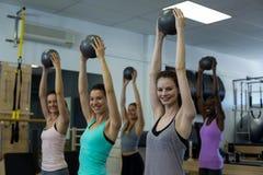 Femmes convenables exécutant étirant l'exercice avec la boule de forme physique dans le gymnase image libre de droits