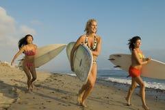 Femmes courant avec des planches de surf Photos stock