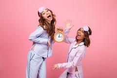 Femmes criardes émotives drôles d'amis dans des pyjamas tenant l'alarme Photographie stock