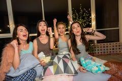 Femmes curieuses semblant le poste TV à la maison Image stock