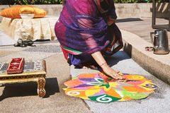 Femmes décorant l'art traditionnel Rangoli de riz sur le plancher pour le mariage indien image libre de droits