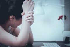 Femmes déprimées s'asseyant dans l'ordinateur avant après la seule tristesse fonctionnante dure émotive et la douleur de bras de  images stock