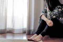 Femmes déprimées s'asseyant près du rideau dans le salon, seul, tristesse, concept émotif photos libres de droits