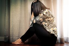 Femmes déprimées s'asseyant près du rideau dans le salon, seul, tristesse, concept émotif images libres de droits
