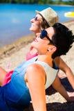 Femmes détendant à la plage de lac Images stock