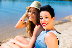 Femmes détendant à la plage de lac Photo stock