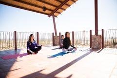 Femmes détendant et méditant dans la classe de yoga Images libres de droits