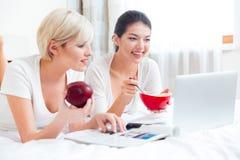 Femmes détendant sur le lit avec la nourriture et l'ordinateur portable Photographie stock