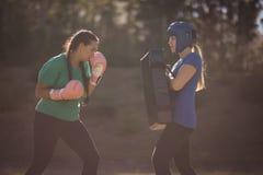 Femmes déterminées pratiquant la boxe pendant le parcours du combattant Images libres de droits