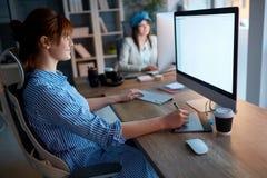 Femmes d'équipe de concepteur travaillant tard sur l'ordinateur au bureau photographie stock libre de droits