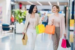 Femmes d'achats parlant les paniers se tenants heureux ayant rire d'amusement Deux belles amies de jeune femme au mail image libre de droits