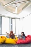 Femmes d'affaires à l'aide des comprimés numériques tout en détendant sur des chaises de sac à haricots dans l'espace de travail  Photographie stock