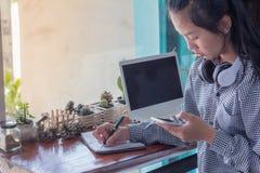 Femmes d'affaires à l'aide du téléphone portable fonctionnant dans le café photos libres de droits