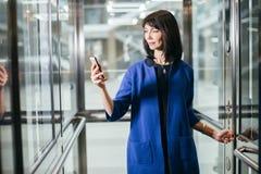 Femmes d'affaires adultes dans le costume utilisant le smartphone Photo stock