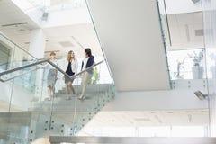 Femmes d'affaires conversant tout en abaissant des étapes dans le bureau Photographie stock