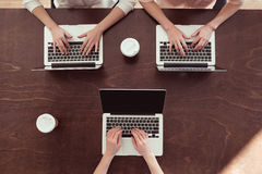 Femmes d'affaires dactylographiant sur des ordinateurs portables à la table Image stock