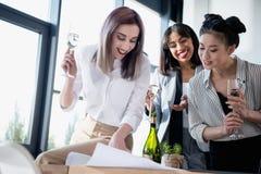 Femmes d'affaires de Multiethic buvant du champagne et regardant sur le modèle Photographie stock libre de droits