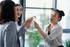 Femmes d'affaires de Multiethic faisant tinter avec des verres et le sourire de champagne Image libre de droits