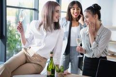 Femmes d'affaires de Multiethic souriant et buvant du champagne au bureau Photographie stock libre de droits