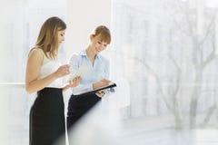 Femmes d'affaires de sourire avec la tablette et le dossier fonctionnant à côté de la clôture dans le bureau Images stock
