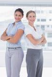 Femmes d'affaires gaies se tenant de nouveau au dos photo libre de droits