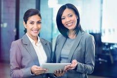 Femmes d'affaires heureuses avec le comprimé numérique Images libres de droits