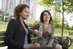 Femmes d'affaires heureuses s'asseyant sur le banc de parc Photographie stock libre de droits