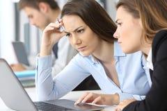Femmes d'affaires inquiétées travaillant sur la ligne images stock
