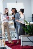Femmes d'affaires multi-ethniques buvant du café et parlant au bureau Images stock