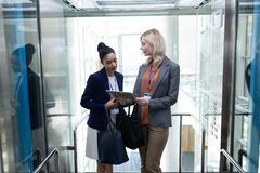 Femmes d'affaires multi-ethniques discutant au-dessus du comprimé numérique dans l'ascenseur de bureau image stock