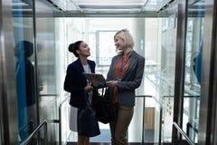 Femmes d'affaires multi-ethniques discutant au-dessus du comprimé numérique dans l'ascenseur de bureau photos libres de droits
