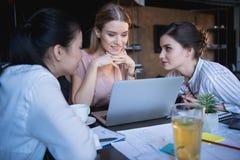 Femmes d'affaires occasionnelles travaillant sur l'ordinateur portable au bureau ensemble Image stock