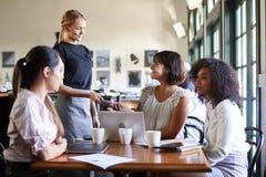 Femmes d'affaires payant Bill At Meeting Around Table dans le caf? image libre de droits