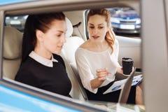 Femmes d'affaires professionnelles futées travaillant dans la voiture Photos libres de droits