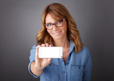femmes d'affaires retenant le relevé mobile de newspaer Images stock