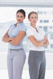 Femmes d'affaires sérieuses se tenant de nouveau au dos image libre de droits