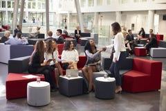 Femmes d'affaires se réunissant dans le lobby occupé du bureau moderne photographie stock libre de droits