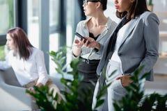 Femmes d'affaires tenant et à l'aide du smartphone avec le collègue s'asseyant derrière Photos stock