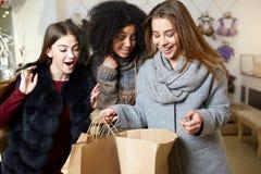 Femmes d'appartenance ethnique diverse avec des paniers posant dans le magasin d'habillement Portrait de trois filles multiracial Photographie stock libre de droits