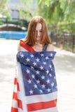 Femmes d'une chevelure assez rouges enveloppées autour avec le drapeau des USA Images libres de droits