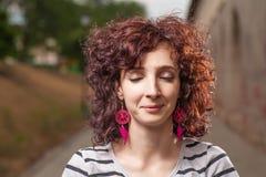 Femmes d'une chevelure bouclées dehors avec ses yeux fermés Joli sourire Image stock