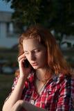 Femmes d'une chevelure rouges au téléphone portable dehors Images stock