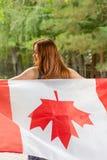 Femmes d'une chevelure rouges avec le drapeau de Canada du dos Photo libre de droits