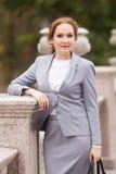 Femmes d'une chevelure rouges d'affaires dans le costume gris Images libres de droits