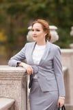 Femmes d'une chevelure rouges d'affaires dans le costume gris Images stock