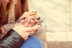 Femmes dactylographiant aux téléphones portables Photographie stock libre de droits