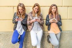 Femmes dactylographiant aux téléphones portables Image stock