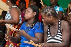 Femmes dactylographiant des morceaux de bois à une cérémonie au village Photographie stock libre de droits