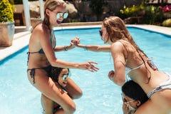 Femmes dans des bikinis ayant l'amusement dans la piscine Image libre de droits