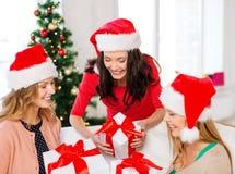 Femmes dans des chapeaux d'aide de Santa avec beaucoup de boîte-cadeau Photographie stock libre de droits